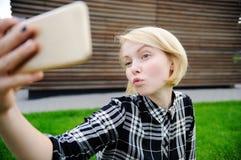 Junge Frau, die selfie mit intelligentem Telefon nimmt Stockfoto