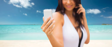 Junge Frau, die selfie mit Smartphone auf Strand nimmt Lizenzfreie Stockfotos