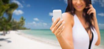 Junge Frau, die selfie mit Smartphone auf Strand nimmt Stockfotos