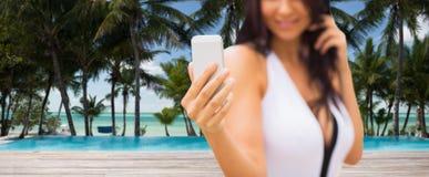 Junge Frau, die selfie mit Smartphone auf Strand nimmt Lizenzfreie Stockbilder