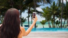 Junge Frau, die selfie mit Smartphone nimmt Lizenzfreie Stockfotos