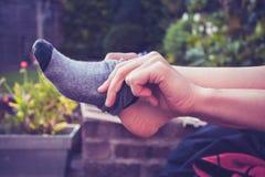 Junge Frau, die sich draußen auf Socken setzt Stockfotografie