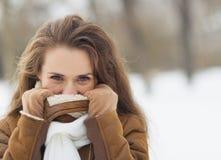 Junge Frau, die sich draußen in der Winterjacke versteckt Lizenzfreie Stockbilder