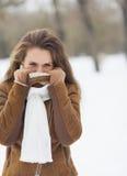 Junge Frau, die sich draußen in der Winterjacke versteckt Stockbild