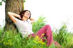 Junge Frau, die sich draußen entspannt Stockfoto