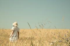 Junge Frau, die sich draußen entspannt Mädchen, das auf einem Gebiet des Weizens mit blauem Himmel bezüglich geht Stockfotos