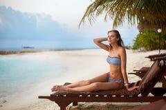 Junge Frau, die sich an in einem Klappstuhl auf einem tropischen Strand bei Sonnenaufgang oder Sonnenuntergang mit stilvollem Str Stockfotografie