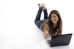 Junge Frau, die sich hinlegt und an Laptop arbeitet stockfotografie