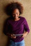 Junge Frau, die sich mit digitaler Tablette hinlegt Stockbild