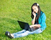 Junge Frau, die sich unter Verwendung eines Laptops hinlegt Lizenzfreies Stockfoto
