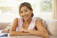 Junge Frau, die sich zu Hause auf Sofa entspannt lizenzfreie stockbilder