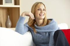 Junge Frau, die sich zu Hause entspannt Stockbilder