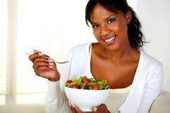 Junge Frau, die Sie beim Essen des Salats betrachtet stockbild