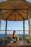 Junge Frau, die - sitzt Meerblick - Modell im Schneidersitz Stockfoto