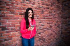 Junge Frau, die Smartphone über Backsteinmauer verwendet Stockbilder