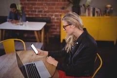 Junge Frau, die Smartphone beim Sitzen mit Laptop an der Kaffeestube verwendet Stockfotos