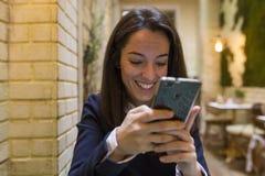 Junge Frau, die Smartphone am breakgast verwendet Stockfotos