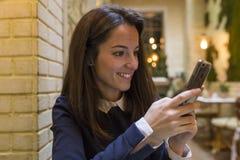 Junge Frau, die Smartphone am breakgast verwendet Lizenzfreies Stockfoto