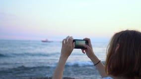 Junge Frau, die Smartphone verwendet, um ein Foto auf dem Strand zu machen stock video footage