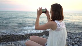 Junge Frau, die Smartphone verwendet, um Foto des Bootes auf Strand zu machen stock video footage