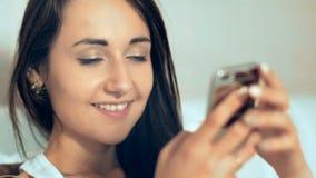Junge Frau, die Smartphone verwendet und auf dem Bett liegt stock video