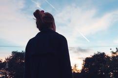 Junge Frau, die Sonnenuntergang im Abstand betrachtet Lizenzfreie Stockfotos