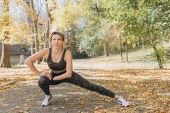 Junge Frau, die in sonnigen Park ausdehnt Eignungsmädchen, das draußen in der Landschaft der Natur ausbildet Konzept des Sports u lizenzfreies stockfoto