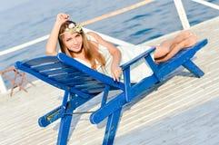Junge Frau, die sonnigen Tag auf Sonnenaufenthaltsraum genießt Stockfoto