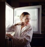 Junge Frau, die spät nach etwas Snack im Kühlschrank nachts sucht stockbild