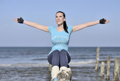 Junge Frau, die Spaß auf dem Strand hat Stockfotos
