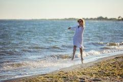 Junge Frau, die Spaß auf Strand hat stockbilder