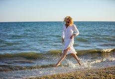 Junge Frau, die Spaß auf Strand hat stockfotografie