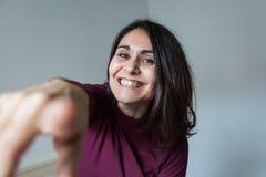 Junge Frau, die Spaß, das Zeigen und das Lächeln hat Lizenzfreies Stockfoto