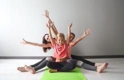 Junge Frau, die Spaß mit den Kindern tun Yoga hat stockfotografie
