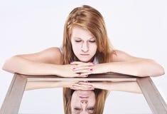 Junge Frau, die Spiegel untersucht Stockfoto