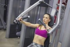 Junge Frau, die stark an der Turnhalle ausbildet Stockfoto