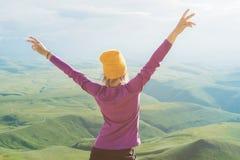 Junge Frau, die stark und auf dem im Freien gegen grünes Tal überzeugt sich fühlt lizenzfreies stockfoto