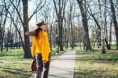Junge Frau, die stilvolle Handtasche hält und gelbe Strickjacke trägt Frühlingsfrauenkleider und -zusätze Art und Weise stockbilder