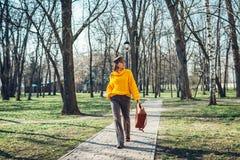 Junge Frau, die stilvolle Handtasche hält und gelbe Strickjacke trägt Frühlingsfrauenkleider und -zusätze Art und Weise lizenzfreie stockbilder