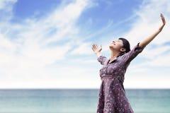Junge Frau, die am Strand ausdehnt Lizenzfreies Stockfoto