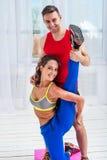 Junge Frau, die streching Übungen mit Mann tut Stockfoto