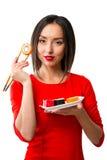 Junge Frau, die Sushi mit Essstäbchen, lokalisiert auf Weiß hält Lizenzfreie Stockfotografie