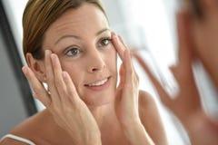 Junge Frau, die tägliche Gesichtscreme aufträgt stockfotos