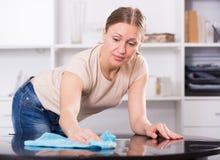 Junge Frau, die Tabelle abwischt Lizenzfreie Stockbilder