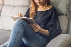 Junge Frau, die Tablette auf Sofa verwendet lizenzfreie stockbilder