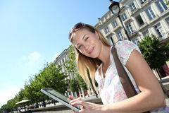 Junge Frau, die Tablette in der Stadt verwendet Stockfoto