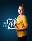 Junge Frau, die Tablette mit Ikonen des Sozialen Netzes hält Lizenzfreie Stockfotos
