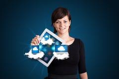 Junge Frau, die Tablette mit modernen Einheiten in den Wolken anhält Lizenzfreie Stockfotos
