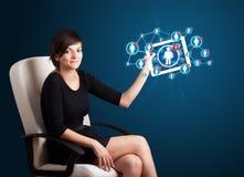 Junge Frau, die Tablette mit Sozialnetzikonen anhält Stockfotografie