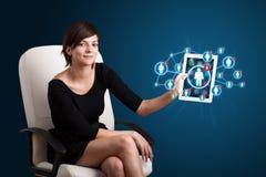 Junge Frau, die Tablette mit Sozialnetzikonen anhält Stockfotos